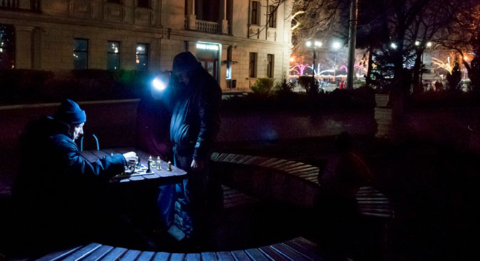 People play chess holding a flashlight near Nakhimov's Square in Sevastopol, Crimea, Dec. 27.