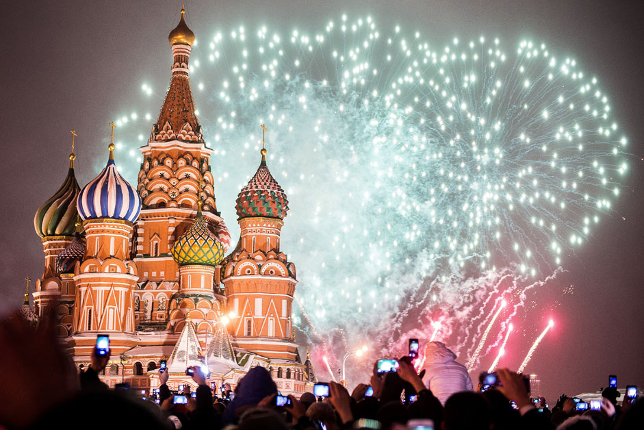 People hold smartphones as they watch fireworks during New Year celebrations at the Red square in Moscow early on January 1
