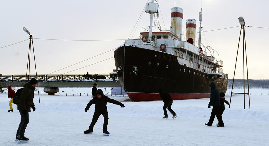 Meluncur di Teluk Beku. Warga bermain ice skating berlatarkan Museum Kapal Pemecah Es Angara di permukaain air teluk yang membeku di Stasiun Pembangkit Listrik Tenaga Air Irkutsk, Kota Irkutsk, Kamis (1/1/15). Bermain ice skating massal merupakakan aktivitas favorit bagi masyarakat lokal. Arena seluncurnya bisa berada di lapangan, halaman komplek apartemen atau sungai beku.