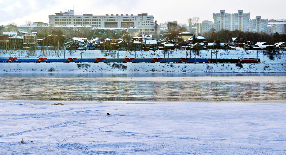 Kereta Trans Siberia. Kereta Trans Siberia melintas di tepi Sungai Angara, Kota Irkutsk, Minggu (4/1/15). Rel Trans Siberia memiliki panjang 9.298 km yang merupakan jalur kereta terpanjang di dunia. Trans Siberia menghubungkan Rusia bagian Eropa, Ural, Siberia dan Timur Jauh Rusia.  Diperlukan waktu tiga hari dan sekian jam dari Kota Irkutsk ke Moskow .  Namun di sepanjang perjalanan, penumpang dapat menikmati sajian keindahan alam Rusia.
