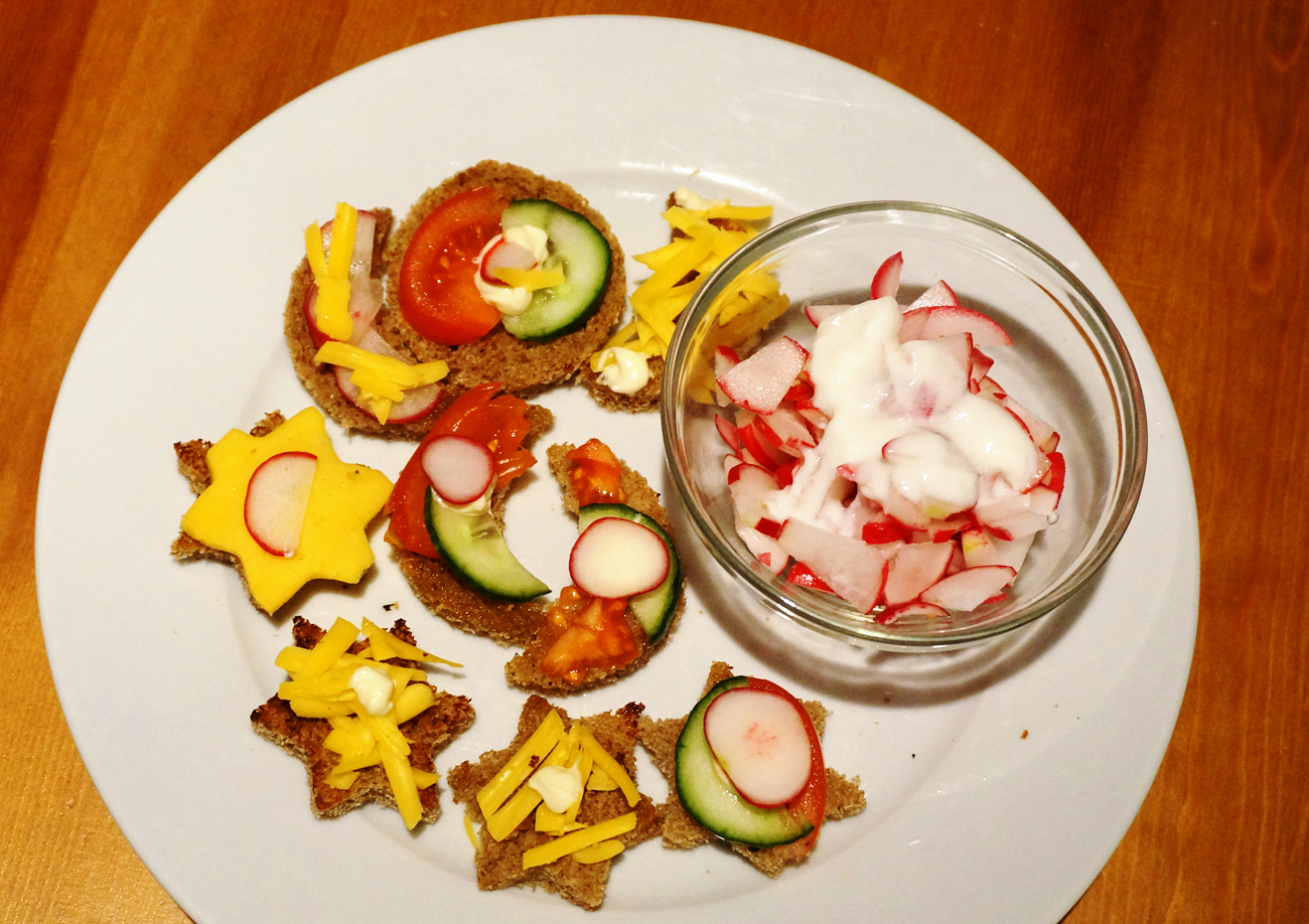 Salad with radishes and sour cream, sandwiches on toasted bread.