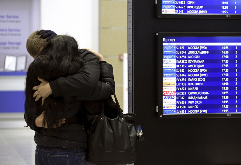 A couple embraces next to a flight information board at Pulkovoairport in St. Petersburg, Russia, October 31, 2015.