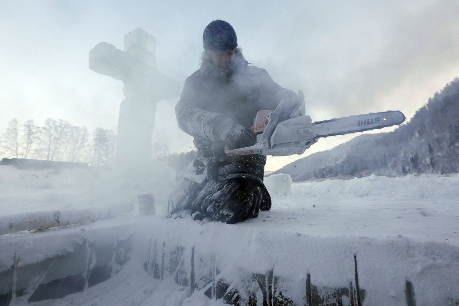 Hieromonch Nikandr from a local male skete operates a chainsaw while preparing an ice hole for the Orthodox Epiphany ceremony on the ice-covered Mana river, with the air temperature at about minus 30 degrees Celsius (minus 22 degrees Fahrenheit), in Taiga area near the Siberian village of Mansky outside Krasnoyarsk, Russia