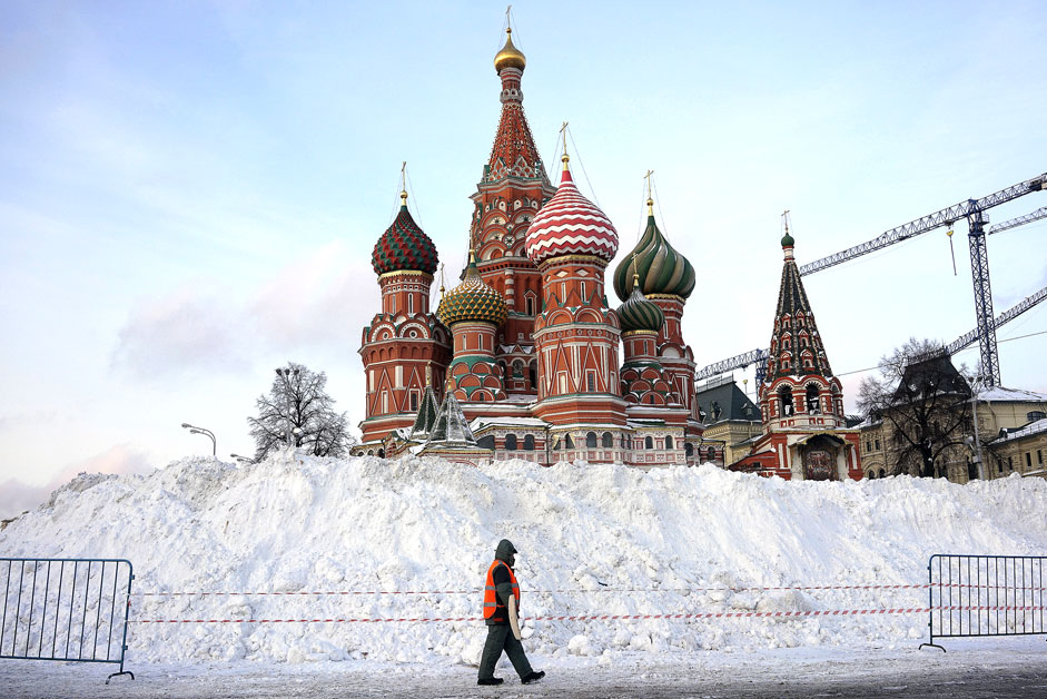 A street sweeper walks past St. Basil's Cathedral at Red Square in Moscow, Russia
