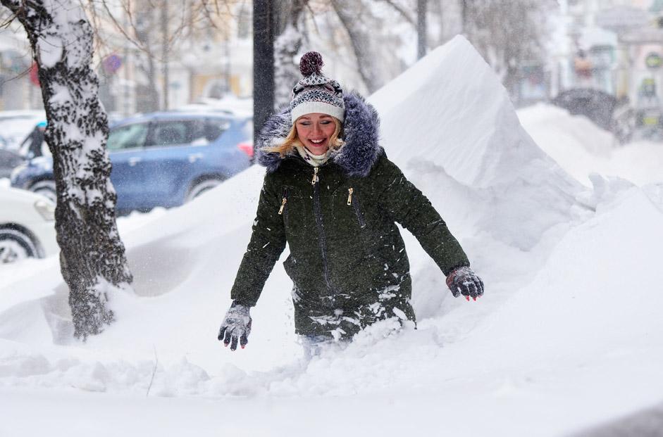 Eine Frau in Wladiwostok kämpft sich durch die Schneemassen. Nach einem Schneesturm sind sie teils mannshoch.