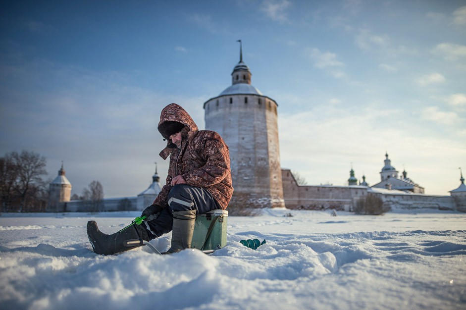 An ice fisherman on the ice of Lake Siverskoye, near the Kirillo-Belozersky Monastery in Vologda Region
