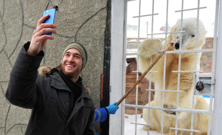 Pavel Francouz, Traktor Ice Hockey Club player, feeding the Club's white bear Altyn charm.