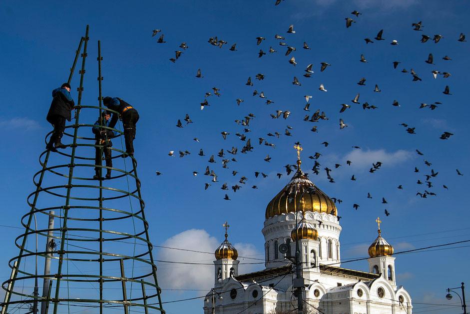 Комунални работници ги симнуваат Божиќните украси пред Соборниот храм Христос Спасителот во Москва.