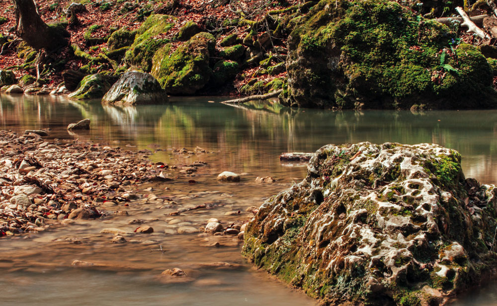 Cette crique étroite mais pourtant torrentielle est entourée de hauts rochers et d'une rare forêt de hêtre.