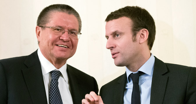 Russian Economics Minister Alexei Ulyukayev, left, and French Economics Minister Emmanuel Macron talk during the Russian-French Council of Economic, Financial, Industrial and Trade Issues session in Moscow, Russia, Monday, Jan. 25, 2016.