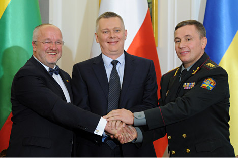 Defence ministers, of Lithuania Juozas Olekas, left, of Poland Tomasz Siemoniak, center, and of Ukraine Lt. Gen. Valeriy Heletei shake hands after signing an act forming a joint military unit, during a ceremony in Warsaw, Poland, Sept. 19, 2014.
