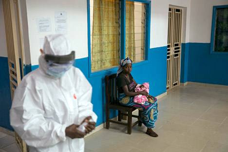A health worker walks past a woman holding a baby at the maternity ward in the government hospital in Koidu, Kono district in eastern Sierra Leone, December 20, 2014.