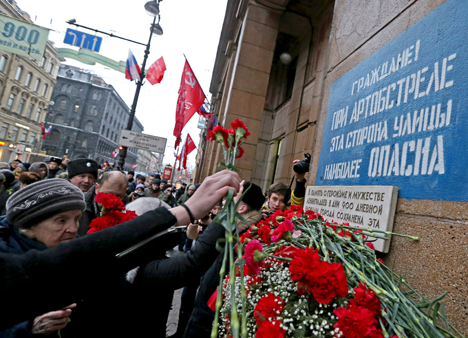 "ST. PETERSBURG, RUSSIA. JANUARY 27, 2016. People laying flowers at building No14 in Nevsky Avenue during celebrations marking the 72nd anniversary of lifting the Siege of Leningrad during World War II. In the wartime, there was a sign on the building reading ""Citizens! During artillery shelling this side of the street is the most dangerous."""