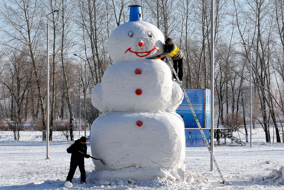 Men work on a 5 meters high snowman at a park in a Siberian city of Krasnoyarsk, Russia