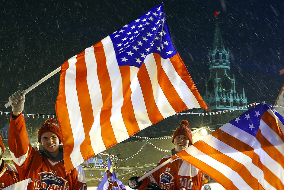 People wave U.S. flags during a hockey match, marking 100 days before the 2016 IIHF World Championship, in Moscow's Red Square, with the Spasskaya Tower of the Kremlin seen in the background, Russia