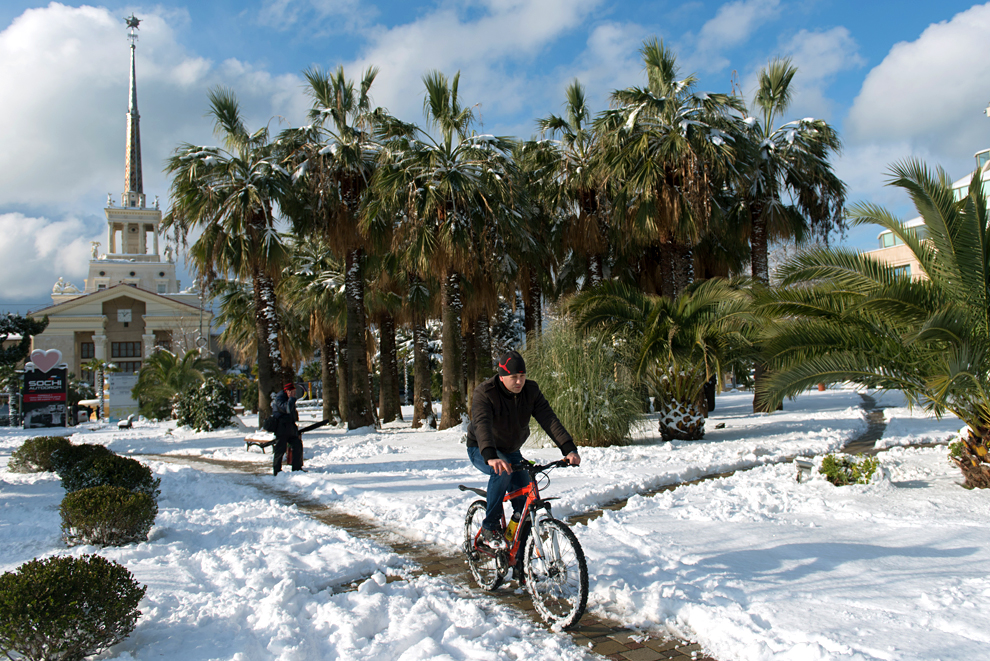 A young man rides a bike through the park near the Marine Station in Sochi.