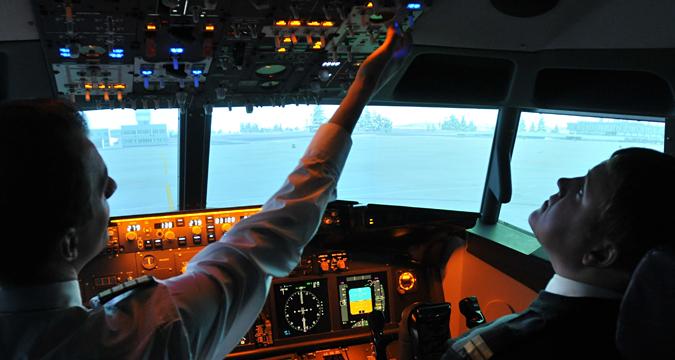 Para siswa melatih diri mereka sendiri melalui simulator pelatihan pilot di Universitas Penerbangan Sipil Sankt Peterburg, Rusia.