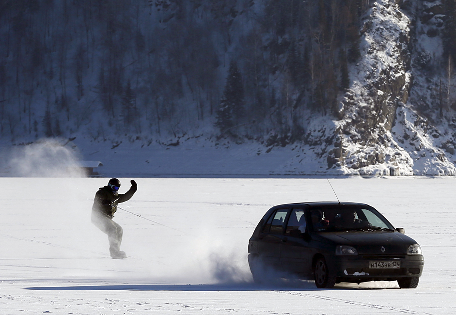 A car tows a snowboarder along the frozen surface of the Yenisei River in Taiga district, with the air temperature at about minus 25 degrees Celsius (minus 13 degrees Fahrenheit), outside Krasnoyarsk, Siberia, Russia, January 31, 2016.
