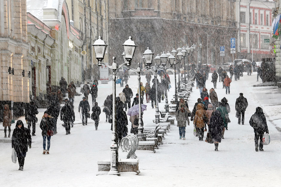 People walk during a snowfall in central Moscow