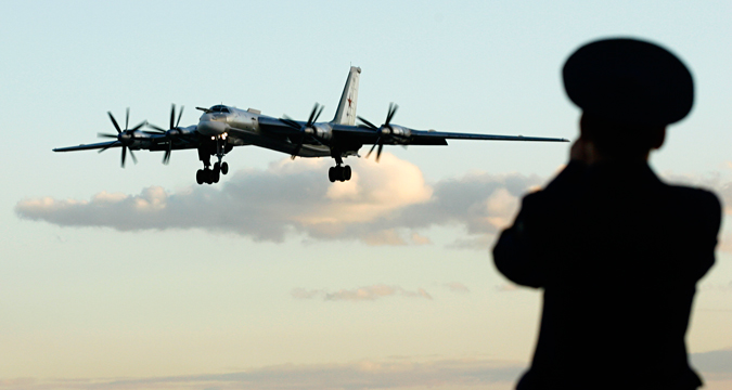A Russian officer takes a picture of a TU-95 bomber, or Bear, at a military airbase in Engels some 900 km (559 miles) south of Moscow August 7, 2008.