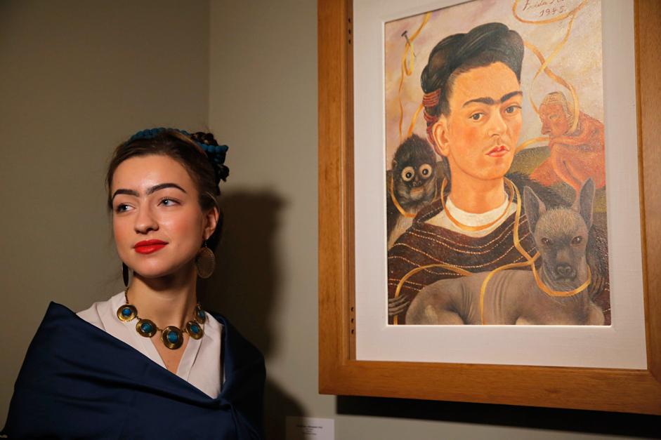 Mujer disfrazada de Frida Kahlo frente a un autorretrato de la pintora mexicana en San Petersburgo.