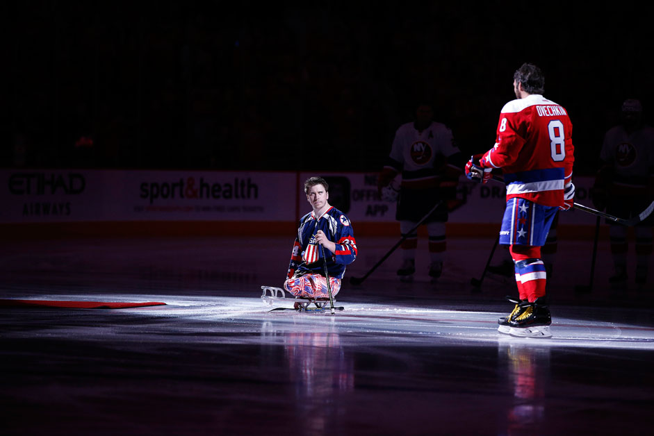 US Marine Corps Lance Corporal Joshua Misiewicz, a member of the USA National sled hockey team, waits for Washington Capitals left wing Alex Ovechkin (8), from Russia, for a pre-game ceremonial puck drop before an NHL hockey game against the New York Islanders