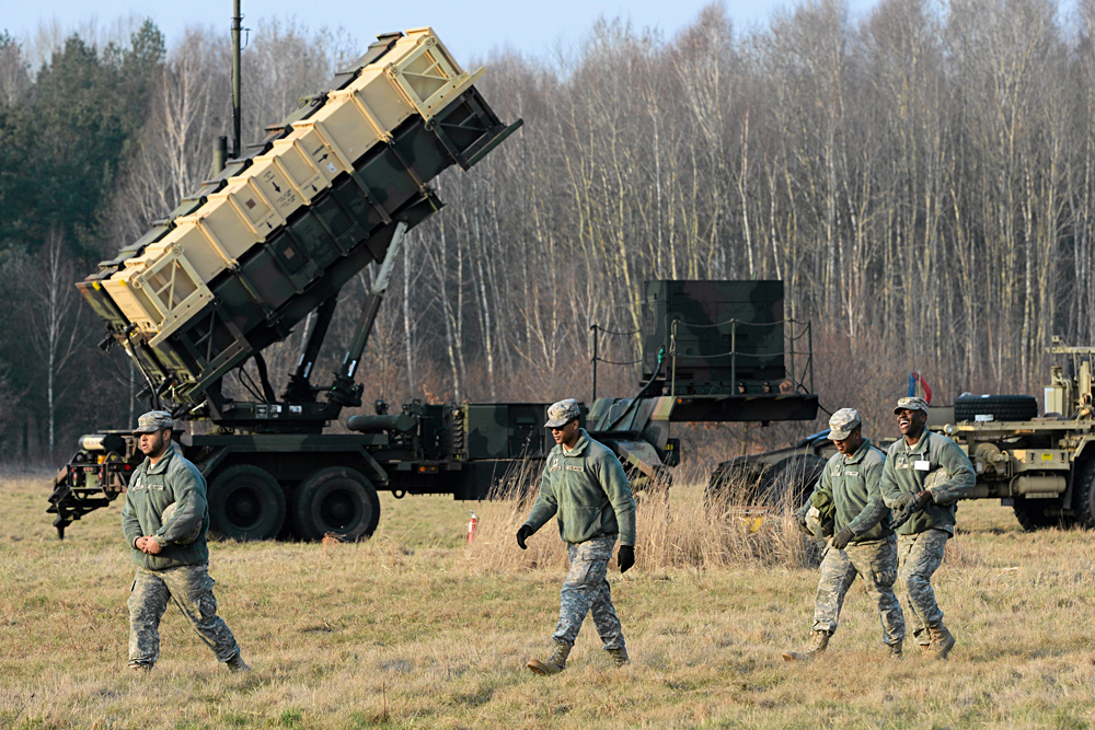U.S. soldiers walk next to a Patriot missile defence battery during join exercises at the military grouds in Sochaczew, near Warsaw, March 21, 2015.