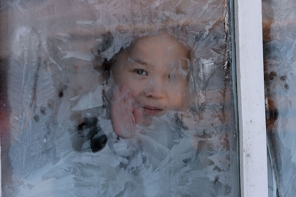 A girl looks through the window of the house on the winter range in Chumur-Oy, Tes-Khem district, Republic of Tuva.