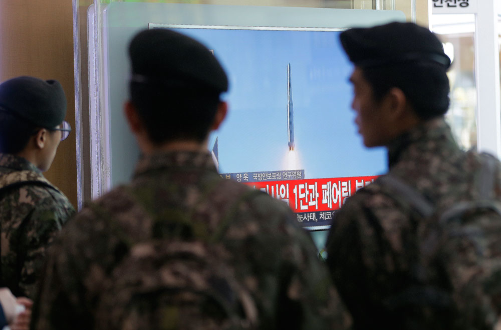 South Korean army soldiers watch a TV news program with a file footage about North Korea's rocket launch.