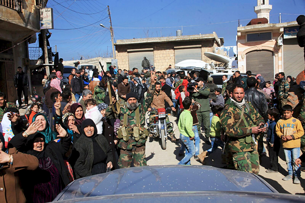 Residents of Nubul and al-Zahraa, along with forces loyal to Syria's President Bashar al-Assad, celebrate after the siege of their towns was broken, northern Aleppo countryside, Syria, in this handout picture provided by SANA on Feb.y 4, 2016.