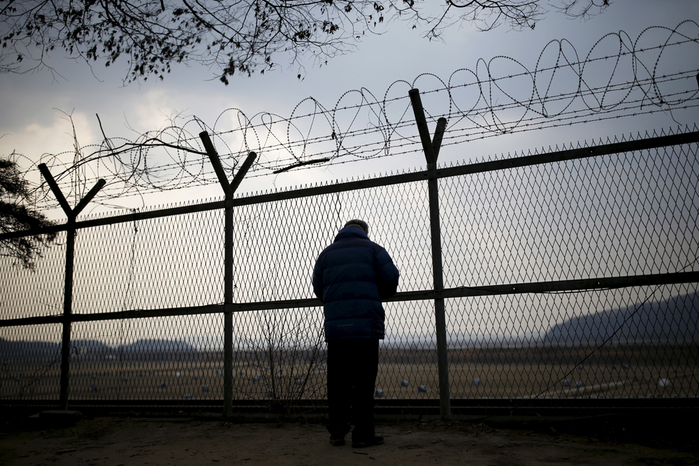 A man looks through a barbed wire fence near the demilitarized zone separating the two Koreas in Paju, South Korea, February 8, 2015.