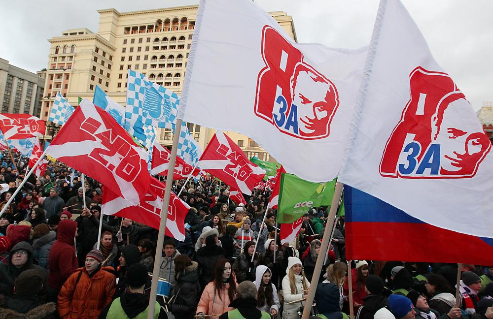 """Anhänger der kremlnahen Jugendorganisation """"Naschi"""" (""""Die Unseren"""") feiern den Sieg der Regierungspartei Einiges Russland bei den letzten Duma-Wahlen im Dezember 2011. """"Ich bin dafür"""", steht auf ihren Flaggen mit Putin-Aufdruck."""