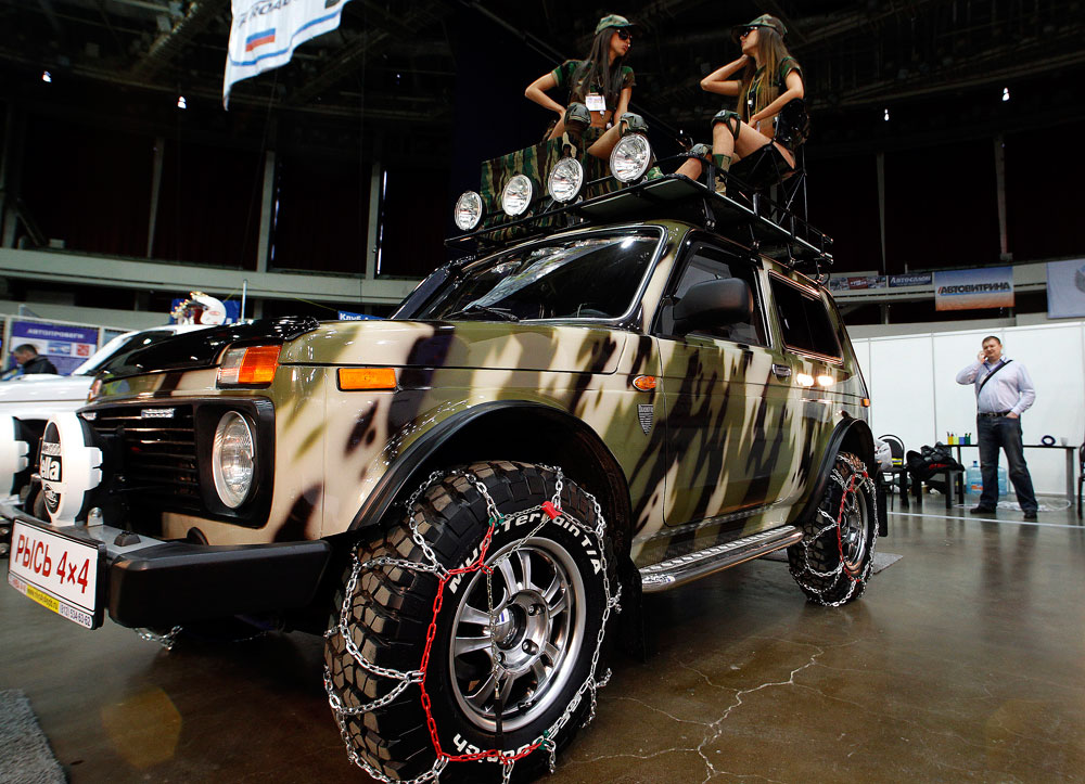 Zwei Models posieren auf einem Lada Niva Lynx auf der internationalen Automobilmesse in Sankt Petersburg.