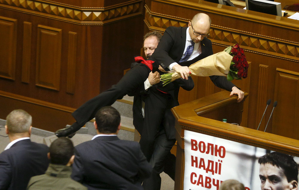 Rada deputy Oleg Barna removes Prime Minister Arseny Yatseniuk from the tribune, after presenting him a bouquet of roses, during the parliament session in Kiev, Ukraine