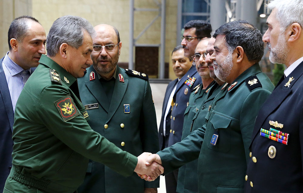 Russia's Defense Minister Sergei Shoigu (L front) meets with an Iranian delegation. Also pictured: Iran's Defense Minister Hossein Dehghan (2nd L background)