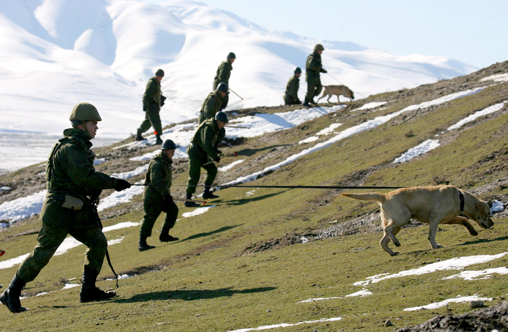 Russian servicemen walk during an operation to search for unexploded military shells, which were used during previous military war games, at the  Lyaur firing ground of Russia's military base number 201 outside Dushanbe, Jan. 17, 2012.