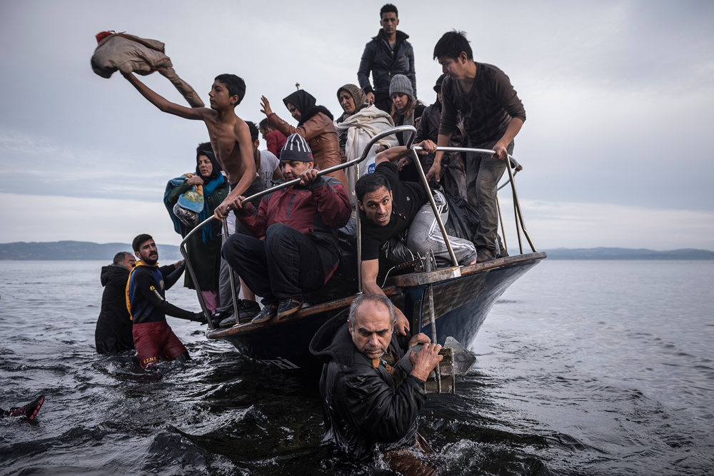 "In this image released by World Press Photo titled ""Reporting Europe's Refugee Crisis"" by photographer Sergey Ponomarev for The New York Times which won the first prize in the General News Stories category shows refugees arriving by boat near the village of Skala on Lesbos, Greece, 16 November 2015."