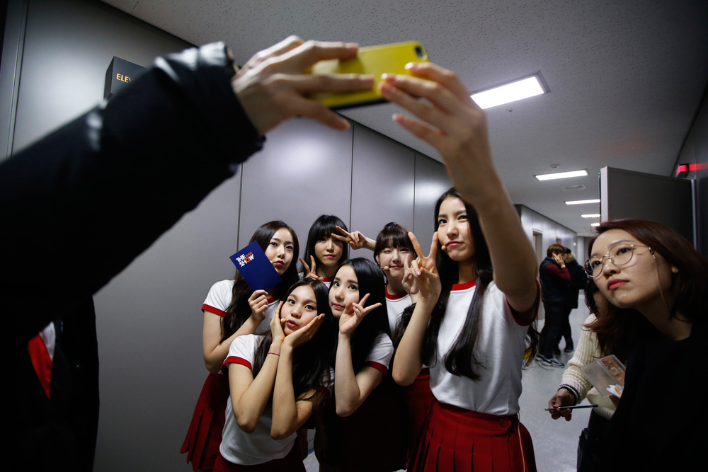 "Members of South Korean girl group GFriend take a 'selfie' after their performance in ""The Show"" in Seoul January 20, 2015."