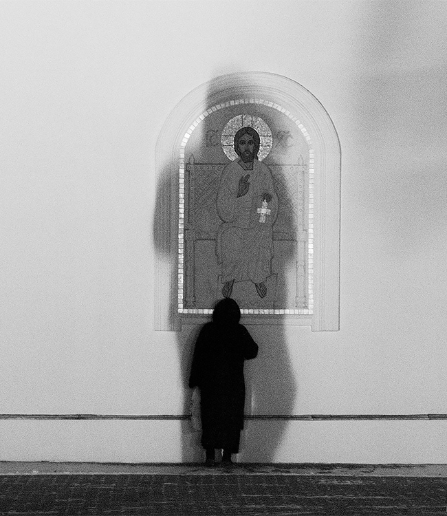 A woman praying in front of a local church during a cold evening.