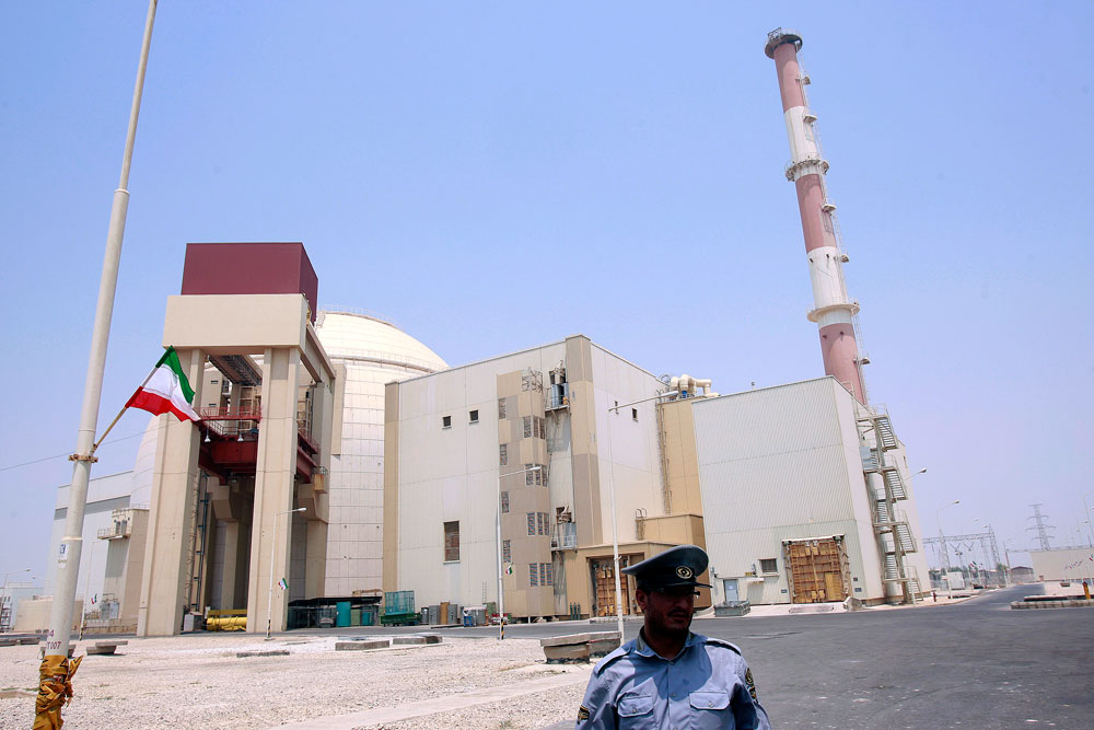 A security official stands in front of the Bushehr nuclear reactor, 746 miles south of Tehran, Aug. 21, 2010.