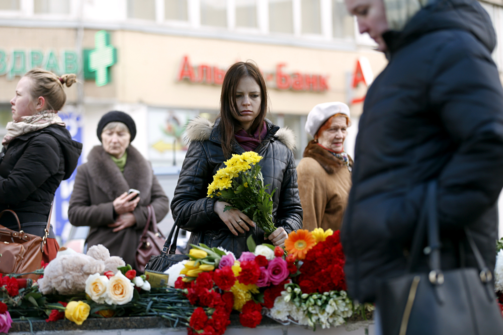 People lay flowers near the Oktyabrskoye Polye station in Moscow.