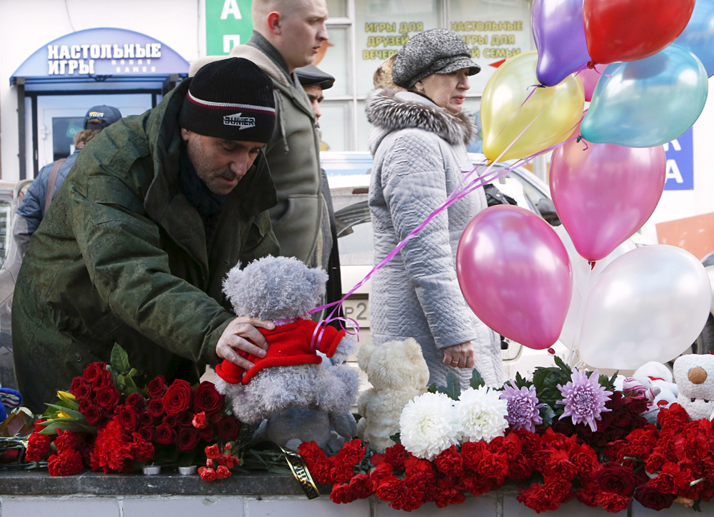 A man places a toy among flowers as people come to commemorate recently murdered child near the Oktyabrskoye Pole metro station in Moscow, March 1, 2016.