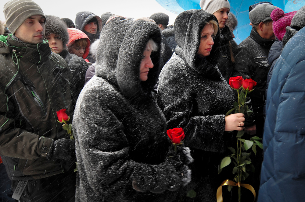 People queue to pay last respects to Vitaly Lavrov, one of the dead miners, during a funeral in Vorkuta, Russia Monday, Feb. 29, 2016. Dozens of people have died at a coal mine where a methane gas leak triggered three explosions and the collapse of the mine.