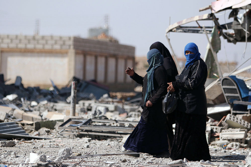 Women walk on rubble in al-Shadadi town, in Hasaka province, Syria.