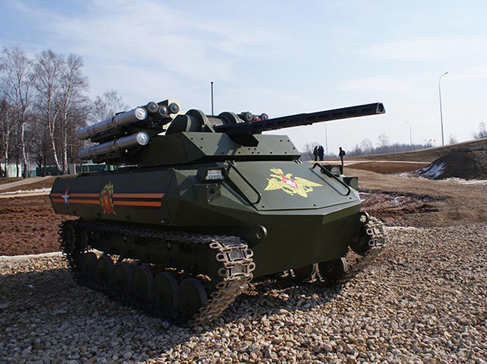 """Уран-9, oфанзивни робот за подршку борбених јединица у градским условима. Наоружан je противтенковским диригованим ракетама """"Атака"""", ПВО ракетама """"Игла"""", аутоматским топом калибра 30 мм, аутоматском пушком калибра 12,7 мм."""