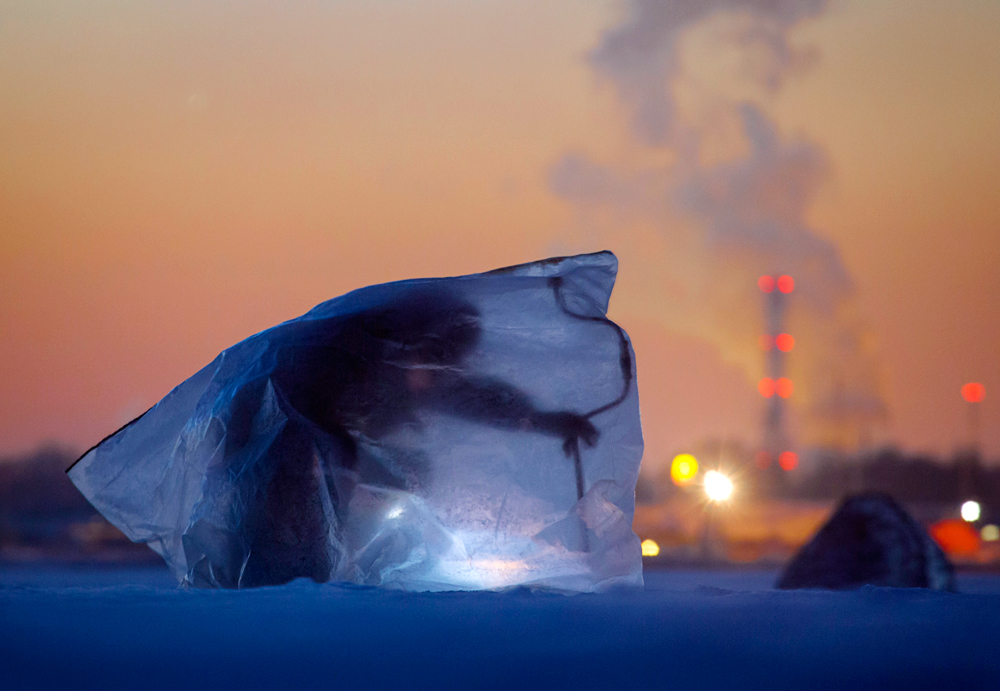 A man covered with plastic bag for protection from the wind and cold, fishes through an ice hole in the Finnish Gulf west of St.Petersburg, Russia