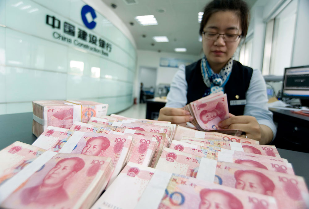 A clerk counts Chinese 100 yuan banknotes at a branch of China Construction Bank in Hai'an, Jiangsu province.