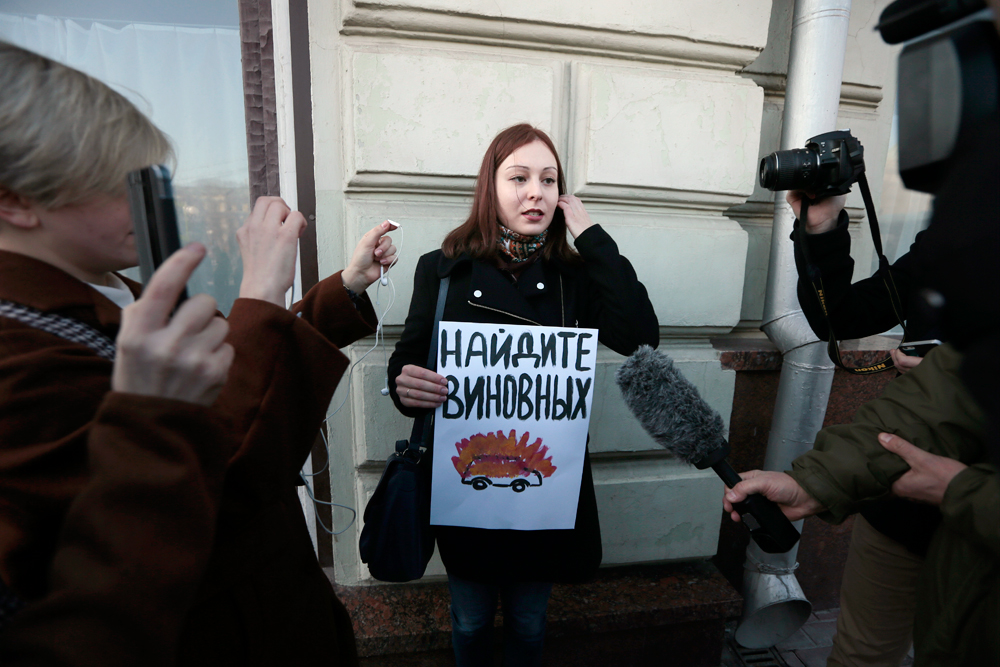 A human rights activist holds a poster as she pickets the Russian President's Administration building in Moscow, March 10. 2016. The poster reads: Find those, who are guilty.