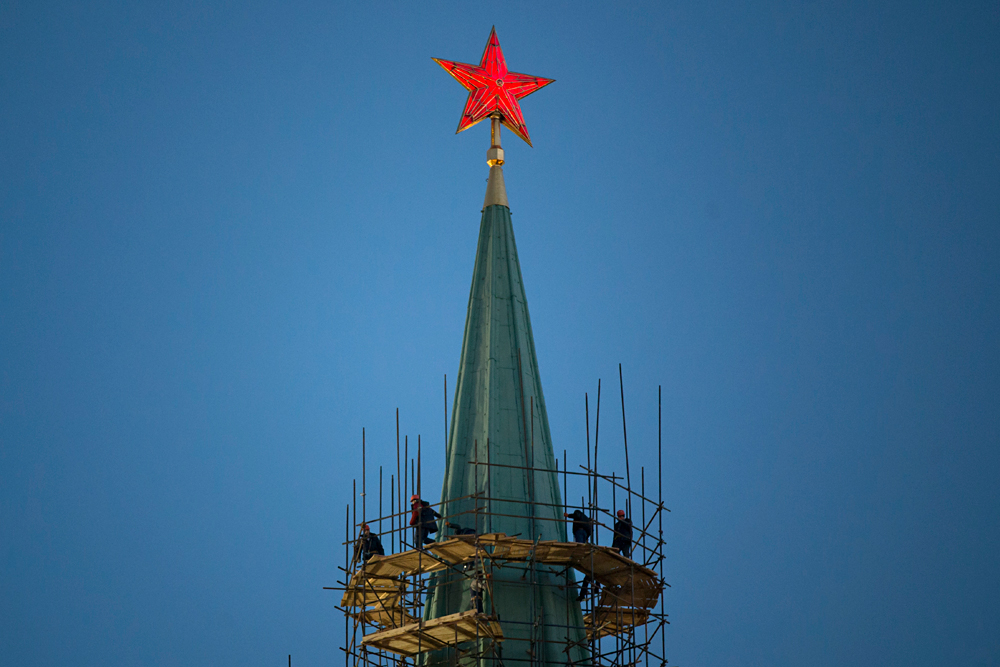 Workers restore a spire of the Nikolskaya Tower in the Kremlin in Moscow, Russia, Thursday, March 10, 2016.