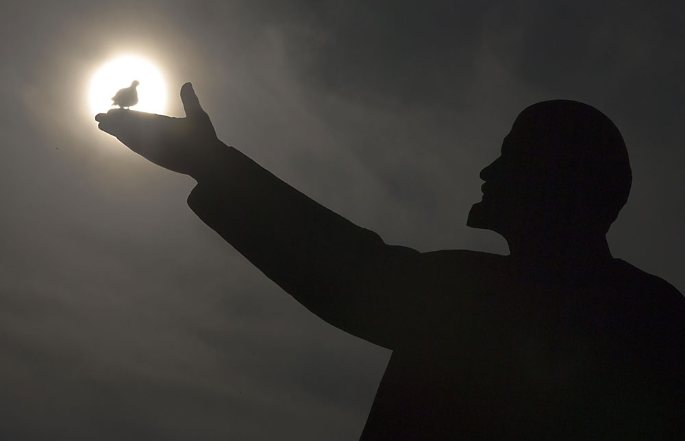 A bird silhouetted by the sun sits on the hand of a statue of Soviet Union founder Vladimir Lenin in Russian leased Baikonur cosmodrome, Kazakhstan, Saturday, March 12, 2016. The start of the new Soyuz mission to the International Space Station is scheduled for Saturday March 19